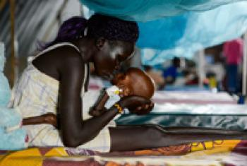 Mother kisses her baby, who is suffering from severe acute malnutrition.