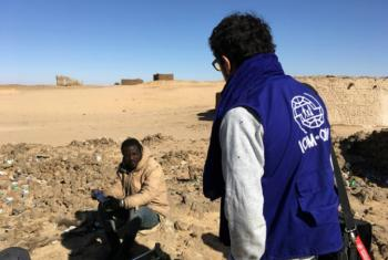 An IOM worker helps a migrant in Seguedine, Niger.