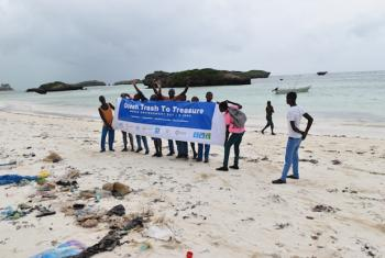 UN Agencies collect ocean trash, including plastics and flip-flops at a beach clean-up in Malindi, Kenya.