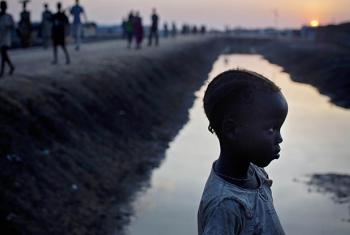 A young girl walks along the edge of a drainage chanel in in the in Protection of Civilian (POC) camp in the evening light in Bentiu, South Sudan.