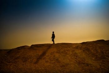 A boy walks on a sand bank surrounding a refugee camp in M'bera, Mauritania.