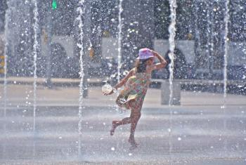 A girl enjoying water fountains amid city summer heat.