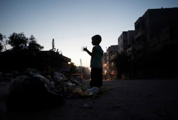 A child stands amid debris in Aleppo, Syria, where cluster munitions continue to be used, according to monitors.