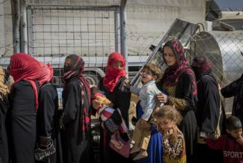 Displaced Iraqi women line up to receive food and water at Debaga camp for internally displaced people in Iraq's Erbil Governorate. File