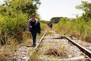 A woman fleeing from El Salvador walks along the train tracks in Chiapas, Mexico on her way to the United States.