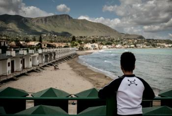 A boy who is an unaccompanied minor looks across the beach in Trabia, Italy. In May 2016, since the beginning of 2016, almost 184,500 people had crossed the Mediterranean to seek safety and protection in Europe.