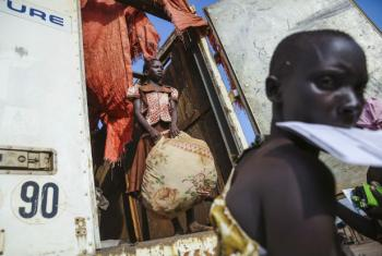Groups gather their belongings from the back of a truck outside the reception center at the Imvepi Refugee camp in Northern Uganda. Uganda is now hosting now more than 1.2 million refugees. Close to 1 million of which are from South Sudan.