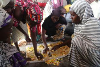 IDP women in one of the camps in Maiduguri, Borno State, Nigeria, collect their share of stock cubes to prepare the day's meal. The women are paid a salary to cook the meals.