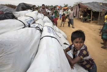 A boy leans against UNHCR tarpaulin, waiting to be distributed at Kutupalong refugee camp. © UNHCR/Paula Bronstein