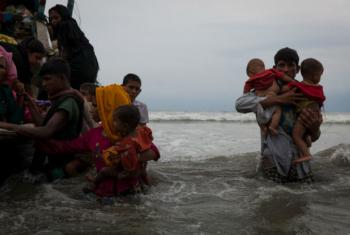 On 7 September 2017, newly arrived Rohingya refugees walk ashore at Shamlapur beach in Cox's Bazar district, Chittagong Division in Bangladesh, after traveling for 5 hours in a boat across the open waters of the Bay of Bengal.