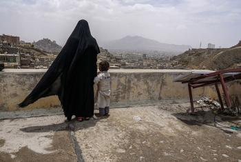 An internally displaced woman and her daughter look over the city of Sana'a, Yemen, from the roof of this dilapidated building they call their new home.
