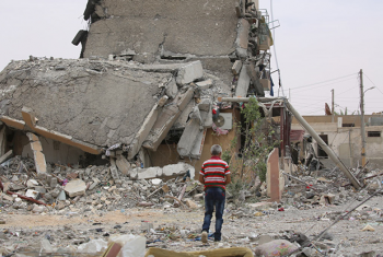 A person walks amid destroyed buildings and rubble in Tabqa city, Raqqa governorate, Syria.