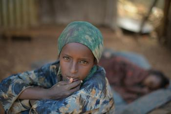 A young girl sits in the shade, while her sister sleeps behind her, at an IDP camp in Baidoa for victims of a drought currently affecting Somalia.