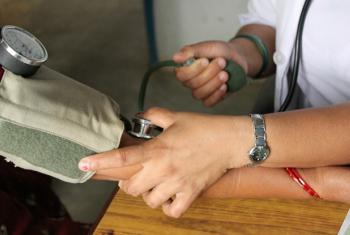 A close-up on hands as skilled health worker takes the blood pressure of a patient.