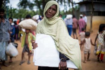 Suruz Jahan, 75, receives a UNHCR tarpaulin in Bangladesh's Kutupalong refugee camp.