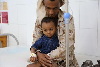 A child suffering from cholera is held by his father as he receives treatment at the Alsadaqah Hospital, Aden, Yemen, 14 August 2017. © UNICEF/UN078078/Mutaz Fuad