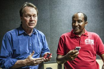 UNAMID Ordnance Disposal Office programme manager Jeffrey McMurdo (left) and staff member Abel Tesfai explain the Solar Powered Risk Education Talking Device, which they are holding.
