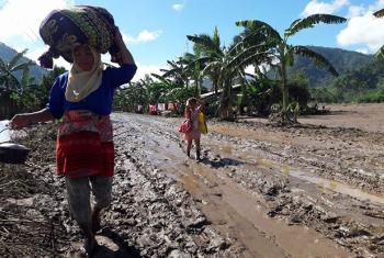 A woman and a child walk with their belongings along a road destroyed by Tropical Storm Tembin in Munai muncipality, Lanao del Norte, north Mindanao, the Philippines.