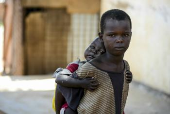 A child carries his younger sister on his back. Both children are living on the street in Aweil, South Sudan. UNICEF/Rich
