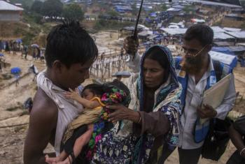 A Rohingya refugee in Bangladesh with her son and granddaughter, accompanied by a volunteer health worker.