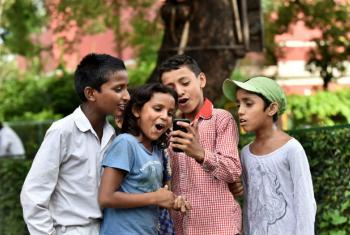 Children at St. Columba's School, Delhi, India, use a mobile phone.