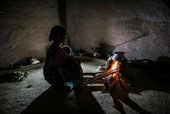 A woman prepares a meal on an indoor stove with her baby in Chhattisgarh, India.