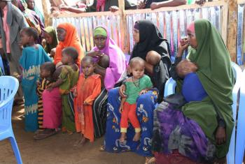 Mothers and their children in a queue waiting to receive measles vaccinations as part of a UNICEF-supported immunization campaign at the Beerta Muuri camp for internally displaced persons in Baidoa, Somalia.