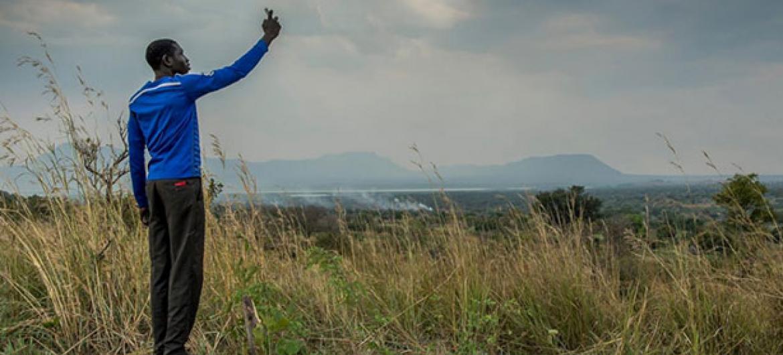 Un joven de Sudán del Sur intenta agarrar cobertura en su móvil en el campo de refugiados de Nyumanzi, al norte de Uganda.