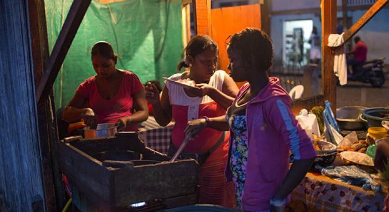 Mujeres administran un restaurante callejero especializado en frituras de pescado en la ciudad portuaria de Tumaco, en el sudoeste de Colombia. El 70% del empleo de las mujeres en las regiones en desarrollo es de carácter informal y carece de protección.