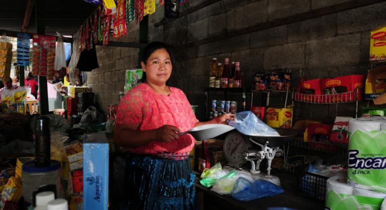 Una mujer vende sus productos en un mercado de Guatemala.