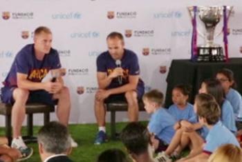 Los jugadores del Barça, Marc-André Ter Stegen (izq.) y el capitán del equipo Andrés Iniesta (centro), durante el evento de UNICEF. Captura de video. UNICEF.