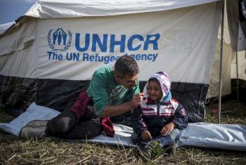 Un refugiado sirio de Aleppo juega con su hijo frente a una tienda de campaña en Hungría. Foto ACNUR/Laban-Mattei.