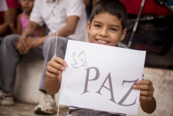 Un niño sujeta un cartel por la paz en el parque de la memoria de El Castillo, en Meta, Colombia. Foto: Mauricio Cardona/PNUD Colombia.