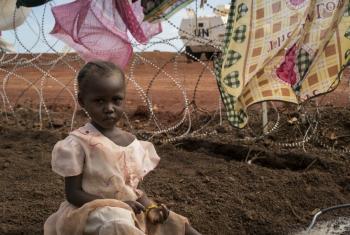 Niema de tres años espera mientras su madre lava ropas. Su familia se desplazó al interior del país tras la violencia desatada en Wau, Sudán del Sur. Foto: UNICEF/Ohanesian.