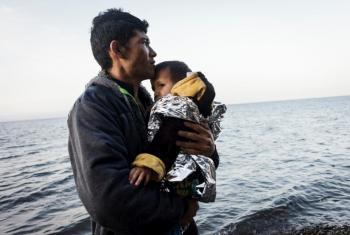 Un refugiado de Afganistán sostiene a su hijo pequeño tras arribar a las costas de la isla de Lesbos en Grecia. Ambos cruzaron el mar Egeo desde Turquía en una balsa inflable repleta de más refugiados Afganos. Foto: ACNUR/Achilleas Zavallis.