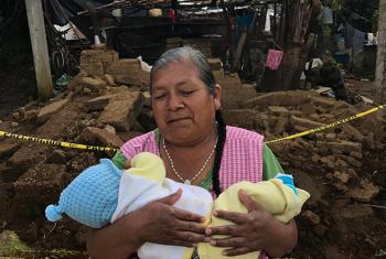 Sabina Pérez Pérez sujeta a su nieto, que todavía no tiene nombre, frente a su casa destruida por el terremoto en San Francisco Xochiteopan, en Puebla, México.