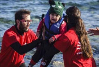 Début 2016, des bénévoles grecs aident un enfant en bas âge à sortir d'un bateau ayant atteint les côtes de l'ile Lesbos, après avoir traversé la mer Égée depuis la Turquie. Photo : HCR / Achilleas Zavallis