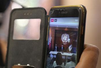 Un journaliste diffusant une conférence de presse en direct sur facebook avec son téléphone portable.