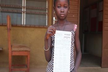 Juliette posant fièrement avec son extrait d'acte de naissance, synonyme de passeport pour l'accès à l'éducation ainsi qu'aux services sociaux de base de son pays, le Bénin (Photo d'archives : HCR/S.Kpandji).
