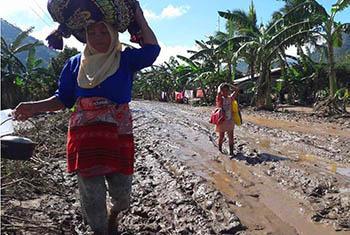 Une femme et un enfant marchent avec leurs biens le long d'une route détruite par la tempête tropicale Tembin à Munai, dans la province de Lanao del Norte, au nord de l'île de Mindanao, aux Philippines.