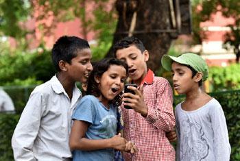 Des enfants de l'école St. Columba's School, Delhi, en Inde, utilisent un téléphone mobile (Crédit
