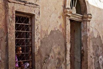 Une fille regarde par la fenêtre de sa maison à Benghazi, en Libye.