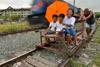 Un train passant un 'trolley', une charrette de fortune en bois, à Manille, aux Philippines. Photo ESCAP/Anthony Into