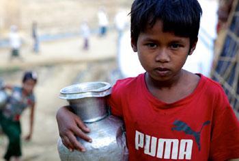 Ukhia, Cox's Bazar, Bangladesh : une fillette rohingya de sept ans rapporte de l'eau vers l'abri de fortune de sa famille après l'avoir remplie à l'aide d'une pompe à eau manuelle dans le camp de Bormapara.