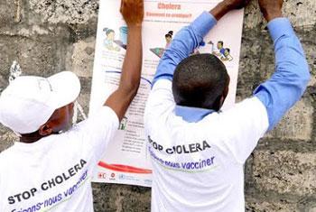 Des mobilisateurs sociaux mettent en place des affiches sur les mesures-clés pour éviter le choléra dans la zone de santé de Pakadjuma touchée par cette épidémie de choléra. Photo OMS/Eugene Kabambi