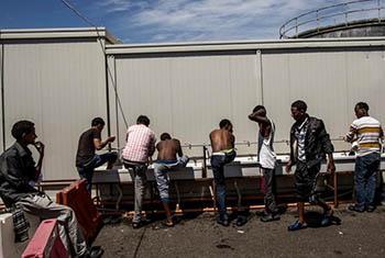 Des réfugiés somaliens et érythréens à l'heure de la toilette dans un centre de réception au port d'Augusta, en Sicile. Ils avaient été secourus en mer par les garde-côtes espagnols après avoir embarqué en Libye. Juin 2015. © HCR / Fabio Bucciarelli