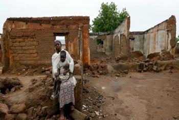 Des rapatriés nigérians assis devant une maison détruite par Boko Haram à Garaha, dans l'Etat d'Adamawa, au Nigéria. Photo d'archives: HCR/George Osod