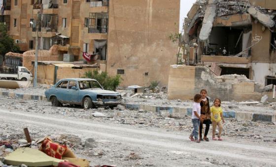 Crianças sírias passeiam no meio da destruição de prédios. Foto: Unicef/Souleiman
