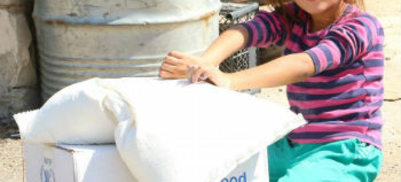 Menina recebe ajuda humanitária. Foto: PMA