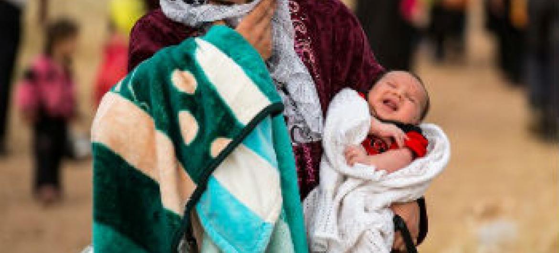 Mulher síria cruza a fronteira com a Jordânia com seu bebê. Foto: Acnur/S. Rich